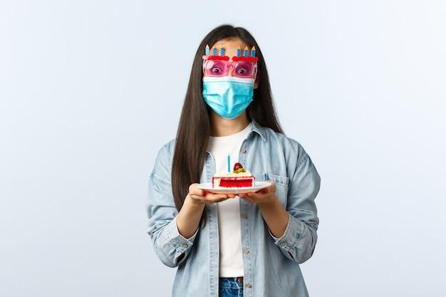 Sociale afstandslevensstijl, covid-19 pandemie, vakantie vieren tijdens het coronavirusconcept. vrolijk feestvarken met medisch masker en feestbril, met verjaardagstaart, genietend van feest