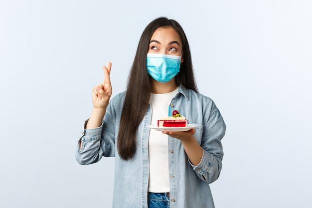 Sociale afstandslevensstijl, covid-19 pandemie, vakantie vieren tijdens het coronavirusconcept. wenselijk schattig verjaardagsmeisje met medisch masker, houd cake vast, doe een wens op verjaardag, kruis vingers veel geluk