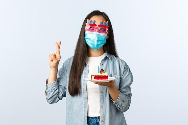Sociale afstandslevensstijl, covid-19 pandemie, vakantieconcept vieren. hoopvol schattig aziatisch verjaardagsmeisje in feestbril en medisch masker, met verjaardagstaart en kruisvingers doen wensen.