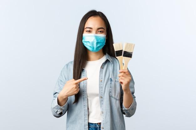 Sociale afstandslevensstijl, covid-19 pandemie, zelfisolatiehobby's en vrijetijdsconcept. leuke artistieke en creatieve aziatische vrouwelijke student die een huis herbouwt, verfborstels laat zien, een masker draagt