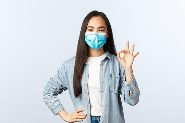 Sociale afstandslevensstijl, covid-19 pandemisch dagelijks leven concept. tevreden zelfverzekerde aziatische meid heeft alles onder controle, garandeert en moedigt alles goed aan met een goed teken, draag een masker
