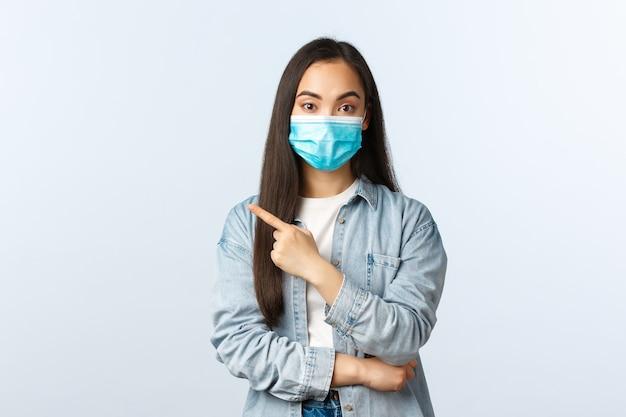 Sociale afstandslevensstijl, covid-19 pandemisch dagelijks leven en vrijetijdsconcept. aantrekkelijk koreaans meisje met medisch masker geeft advies, raad aan om naar de winkel te gaan, wijzende vinger naar links naar banner.