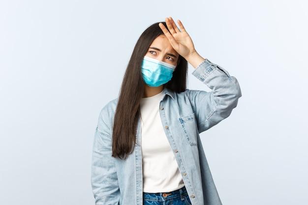 Sociale afstandslevensstijl, covid-19 pandemisch dagelijks leven en vrijetijdsconcept. aziatisch meisje in medische mas voelt zich ziek, raakt het voorhoofd aan, heeft koorts en vermoeidheid, kijkt bedroefd weg.