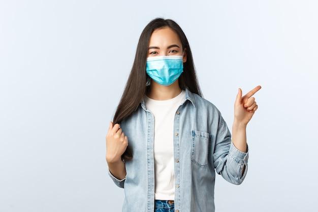 Sociale afstandslevensstijl, covid-19 pandemisch dagelijks leven en vrijetijdsconcept. blij, gelukkig aziatisch meisje dat haar aanraakt, moet een nieuw kapsel maken, met de vinger wijzend naar de promo van de schoonheidssalon.