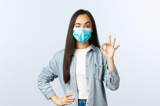 Sociale afstandslevensstijl, covid-19 pandemisch dagelijks leven en vrijetijdsconcept. blij kalm en zelfverzekerd aziatisch meisje met medisch masker, knipoog en toon goed teken in goedkeuring, garantie kwaliteit.