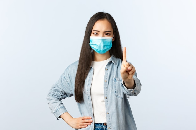 Sociale afstandslevensstijl, covid-19 pandemisch dagelijks leven en vrijetijdsconcept. boos ontevreden aziatisch meisje in medisch masker dat persoon uitscheldt, vinger laat zien, iemand verbiedt of waarschuwt