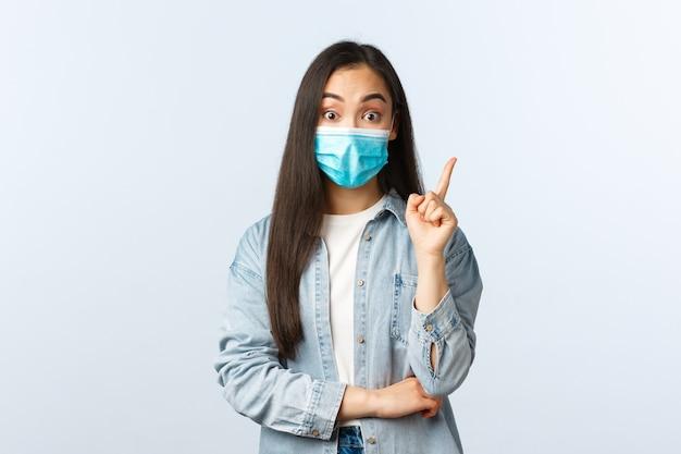 Sociale afstandslevensstijl, covid-19 pandemisch dagelijks leven en vrijetijdsconcept. creatief aziatisch meisje kreeg een idee, draag een medisch masker en hijgde zoals het plan was, hef wijsvinger eureka-gebaar op