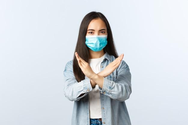 Sociale afstandslevensstijl, covid-19 pandemisch dagelijks leven en vrijetijdsconcept. ernstig ontevreden aziatisch meisje met medisch masker dat een kruisteken toont, iets afkeurt of verbiedt, zeg dat je moet stoppen