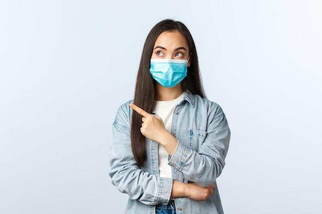 Sociale afstandslevensstijl, covid-19 pandemisch dagelijks leven en vrijetijdsconcept. geïntrigeerde mooie aziatische vrouw in medisch masker adverteren banner, wijzende vinger naar links