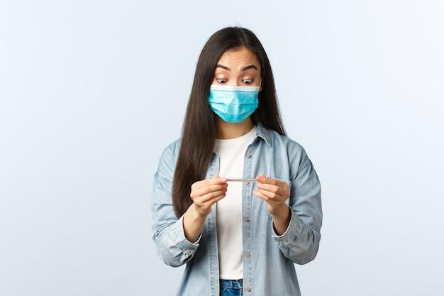 Sociale afstandslevensstijl, covid-19 pandemisch dagelijks leven en vrijetijdsconcept. geschokt aziatisch meisje met medisch masker meet temperatuur met thermometer, verbaasd starend naar resultaat