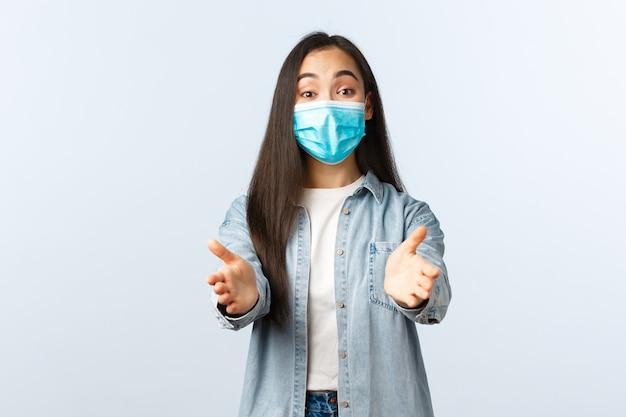 Sociale afstandslevensstijl, covid-19 pandemisch dagelijks leven en vrijetijdsconcept. glimlachende aziatische vrouw met medisch masker die handen naar voren reikt om iets schattigs te nemen of vast te houden.