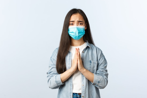 Sociale afstandslevensstijl, covid-19 pandemisch dagelijks leven en vrijetijdsconcept. hoopvolle bezorgde vrouwelijke aziatische student met medisch masker die bidt en smeekt om een vriend die de coronavirusziekte oploopt.