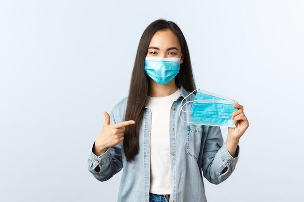 Sociale afstandslevensstijl, covid-19 pandemisch dagelijks leven en vrijetijdsconcept. leuk vriendelijk aziatisch meisje dat een medisch masker toont en uitlegt hoe belangrijk het is om het te dragen tijdens de uitbraak van het coronavirus