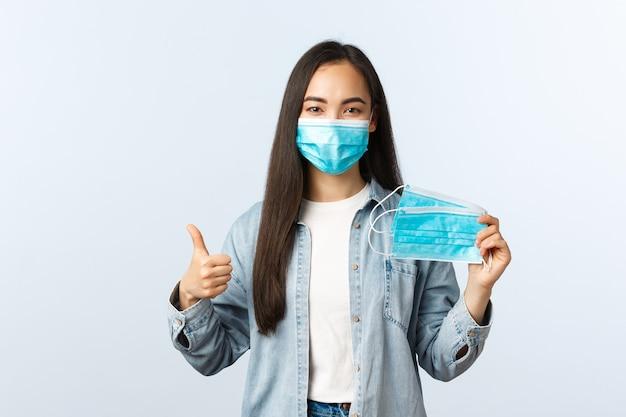 Sociale afstandslevensstijl, covid-19 pandemisch dagelijks leven en vrijetijdsconcept. leuk vriendelijk aziatisch meisje met medisch masker en duim omhoog, raad aan om de gezondheid te beschermen tegen de ziekte van het coronavirus.