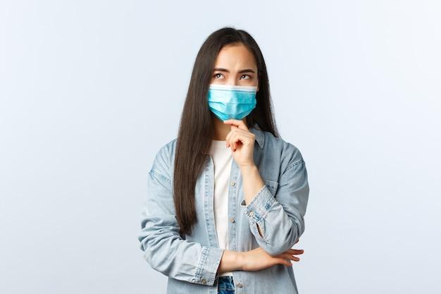 Sociale afstandslevensstijl, covid-19 pandemisch dagelijks leven en vrijetijdsconcept. nadenkend bezorgd aziatisch meisje dat aan een plan denkt, een medisch masker draagt, een serieus gezicht overweegt, omhoog kijkt