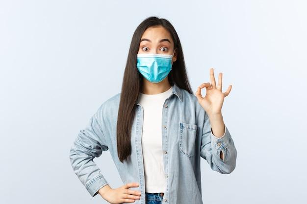 Sociale afstandslevensstijl, covid-19 pandemisch dagelijks leven en vrijetijdsconcept. onder de indruk meisje met medisch masker toont een goed gebaar en kijkt verrast, tevreden met mooie nieuwe kortingen.