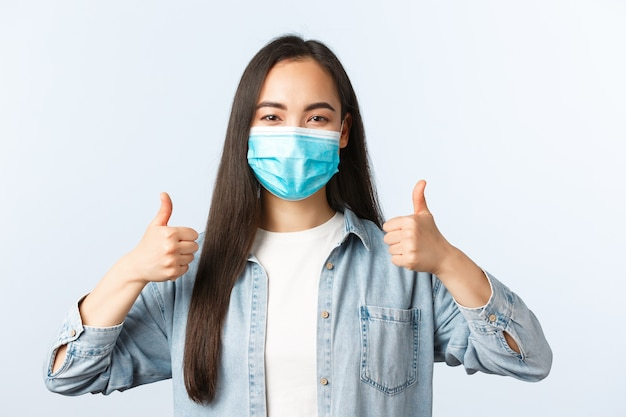 Sociale afstandslevensstijl, covid-19 pandemisch dagelijks leven en vrijetijdsconcept. ondersteunende enthousiaste aziatische vrouw met medisch masker duimen omhoog, pbm dragend terwijl ze boodschappen gaat doen