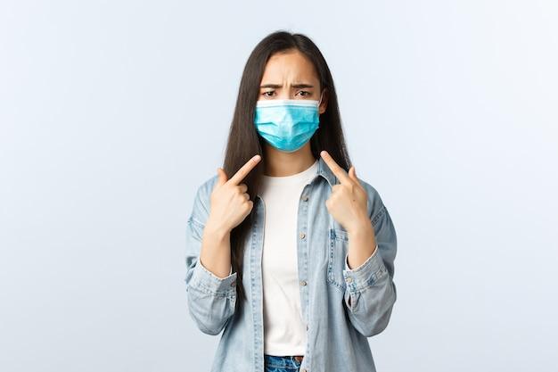 Sociale afstandslevensstijl, covid-19 pandemisch dagelijks leven en vrijetijdsconcept. ontevreden en gehinderd aziatisch meisje dat naar het gezicht wijst met een medisch masker omdat het niet leuk is om het in de zomer te dragen.