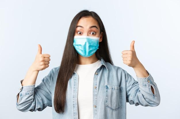 Sociale afstandslevensstijl, covid-19 pandemisch dagelijks leven en vrijetijdsconcept. opgewonden en verrast schattig aziatisch meisje toont duimen, draagt een medisch masker, onder de indruk van geweldige kwaliteit, aan te bevelen.