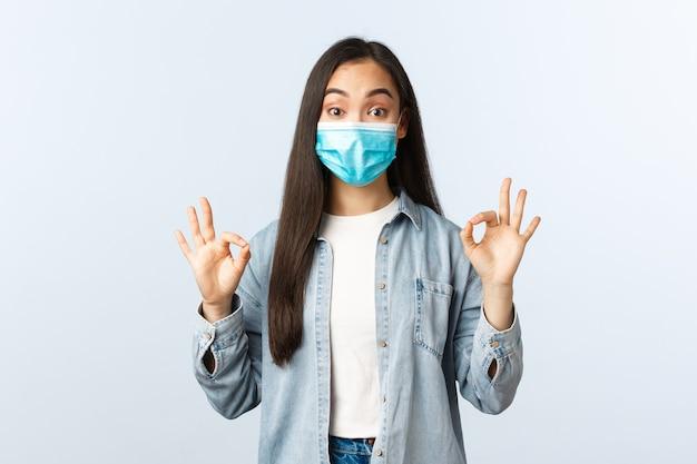 Sociale afstandslevensstijl, covid-19 pandemisch dagelijks leven en vrijetijdsconcept. opgewonden onder de indruk aziatische vrouw met medisch masker met goede tekens ter goedkeuring, klant raadt winkel aan