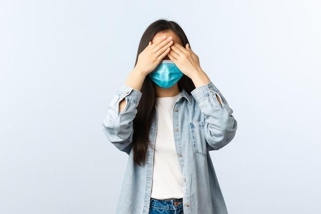 Sociale afstandslevensstijl, covid-19 pandemisch dagelijks leven en vrijetijdsconcept. schattig aziatisch meisje met medisch masker en casual outfit sluit ogen met handen, speelt verstoppertje of anticipeert op verrassing.