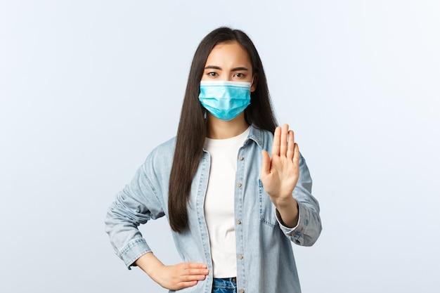 Sociale afstandslevensstijl, covid-19 pandemisch dagelijks leven en vrijetijdsconcept. serieus uitziend aziatisch meisje toont stopgebaar, houd afstand tijdens coronavirus, draag medisch masker
