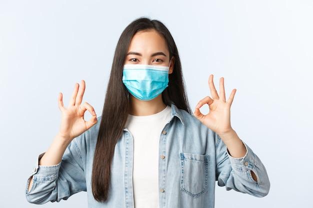 Sociale afstandslevensstijl, covid-19 pandemisch dagelijks leven en vrijetijdsconcept. tevreden aziatische vrouw met medisch masker zegt geen probleem, stemt ermee in of keurt kwaliteit goed, met een goed gebaar blij.