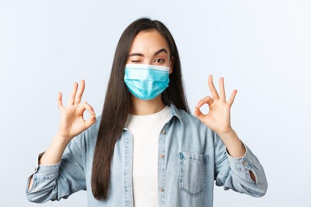 Sociale afstandslevensstijl, covid-19 pandemisch dagelijks leven en vrijetijdsconcept. tevreden vrouwelijke klant met medisch masker beoordeelt goede preventiemaatregelen in de supermarkt, toont goed teken in goedkeuring.
