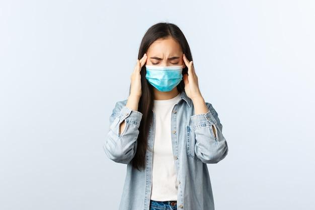 Sociale afstandslevensstijl, covid-19 pandemisch dagelijks leven en vrijetijdsconcept. verontrust aziatisch meisje kreeg een positieve coronavirus-test, voelde zich ziek, droeg een medisch masker, had hoofdpijn of migraine.