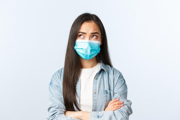 Sociale afstandslevensstijl, covid-19 pandemisch dagelijks leven en vrijetijdsconcept. verontrust doordacht aziatisch meisje met een medisch masker dat iets afbeeldt, linksboven in de hoek kijkt, denkt, bezorgd is.