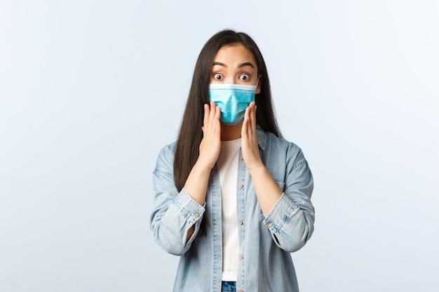 Sociale afstandslevensstijl, covid-19 pandemisch dagelijks leven en vrijetijdsconcept. verrast verbaasd aziatisch meisje dat onder de indruk is, een medisch masker draagt, reageert op geweldig nieuws, zeg wow.