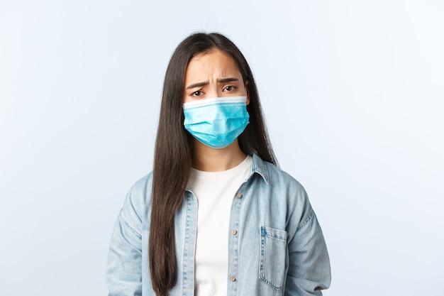 Sociale afstandslevensstijl, covid-19 pandemisch dagelijks leven en vrijetijdsconcept. verstoord somber aziatisch meisje met medisch masker dat bezorgd kijkt, empathie toont, fronst, positieve test coronavirus heeft