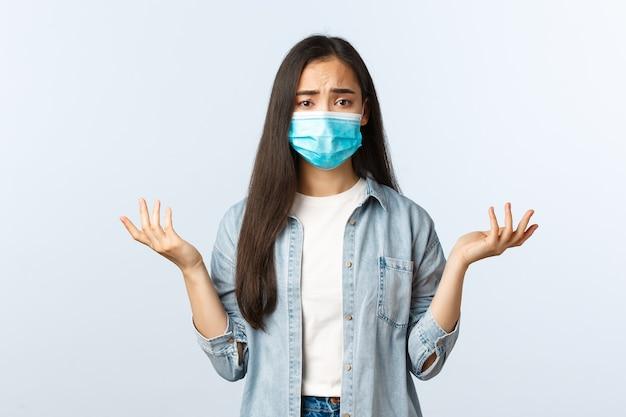 Sociale afstandslevensstijl, covid-19 pandemisch dagelijks leven en vrijetijdsconcept. verwarde en besluiteloze aziatische vrouw die de schouders ophaalt, de handen perplex opsteekt en een medisch masker draagt.