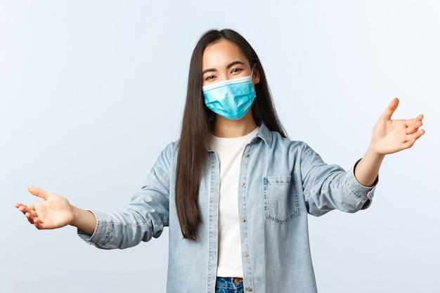 Sociale afstandslevensstijl, covid-19 pandemisch dagelijks leven en vrijetijdsconcept. vriendelijk lachend aziatisch meisje strekt haar handen uit om een knuffel te geven, iemand te omhelzen of welkom te heten, kom naar binnen, draag een medisch masker