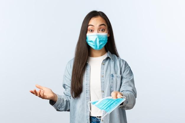 Sociale afstandslevensstijl, covid-19 pandemisch dagelijks leven en vrijetijdsconcept. vriendelijk schattig aziatisch meisje dat je medische maskers geeft om de gezondheid te beschermen tegen coronavirus terwijl je buiten boodschappen doet.