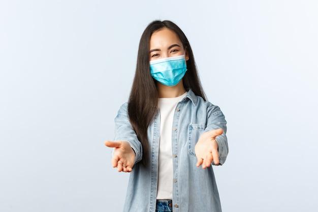 Sociale afstandslevensstijl, covid-19 pandemisch dagelijks leven en vrijetijdsconcept. vriendelijke, mooie aziatische vrouw met een medisch masker die de handen naar voren reikt om iets te pakken of vast te houden, witte achtergrond