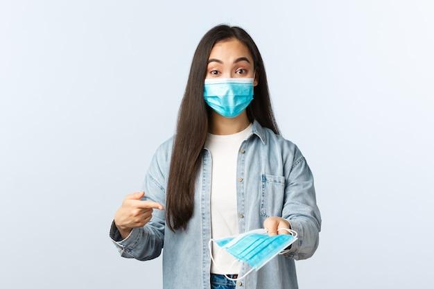 Sociale afstandslevensstijl, covid-19 pandemisch dagelijks leven en vrijetijdsconcept. vrolijk schattig aziatisch meisje legt het belang uit van een medisch masker tijdens de uitbraak van de coronavirusziekte