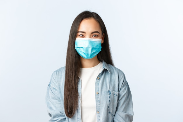 Sociale afstandslevensstijl, covid-19 pandemisch dagelijks leven en vrijetijdsconcept. vrolijk schattig aziatisch meisje met medisch masker dat tijdens de uitbraak van het coronavirus in zelfquarantaine blijft.