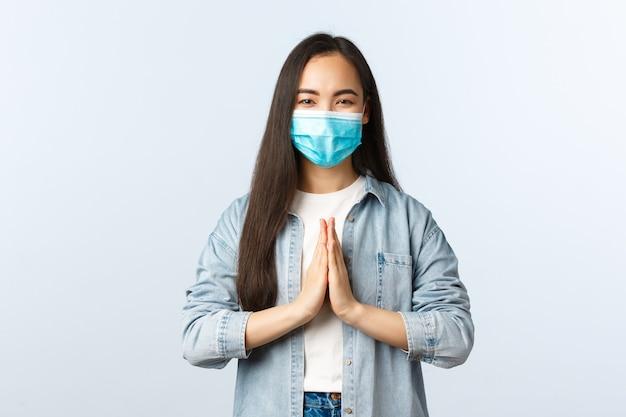 Sociale afstandslevensstijl, covid-19 pandemisch dagelijks leven en vrijetijdsconcept. vrolijke zorgeloze aziatische vrouw met medisch masker zegt namaste, hand in hand in smeekgebaar en glimlachend