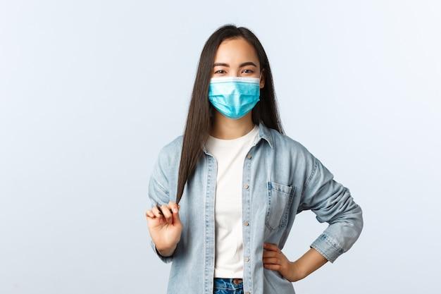Sociale afstandslevensstijl, covid-19 pandemisch dagelijks leven en vrijetijdsconcept. zelfverzekerde vrolijke aziatische vrouw met medisch masker die haar aanraakt en glimlacht, afstand houdt terwijl ze met een vriend praat.