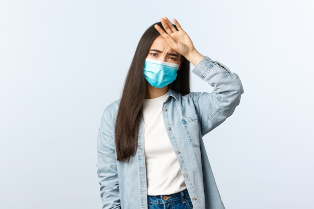 Sociale afstandslevensstijl, covid-19 pandemisch dagelijks leven en vrijetijdsconcept. zieke jonge aziatische vrouw met medisch masker heeft symptomen van het coronavirus, raakt het voorhoofd aan en lijdt aan hoge koorts.