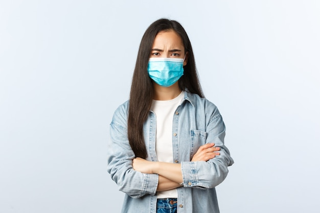 Sociale afstandslevensstijl, covid-19 pandemisch leven en vrijetijdsconcept. verdacht en teleurgesteld jong meisje met medisch masker, aziatische vrouw die er ontevreden uitziet, armen over elkaar kruist en fronst.