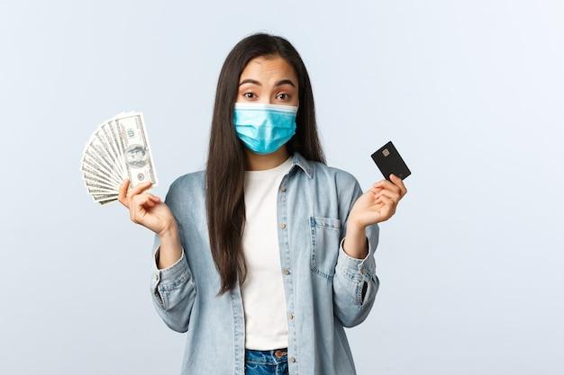 Sociale afstandslevensstijl, covid-19 pandemische zaken en werkgelegenheidsconcept. besluiteloos schattig aziatisch meisje met medisch masker dat de schouders ophaalt terwijl ze contante dollars en creditcard vasthoudt