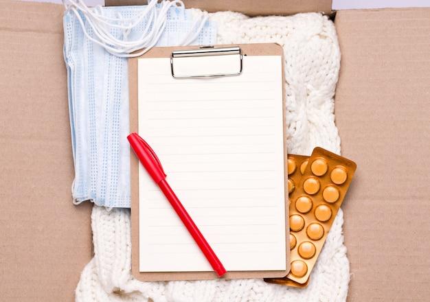 Sociale bijstand concept. in een kartonnen doos zit een leeg formulier, dingen, medicijnen