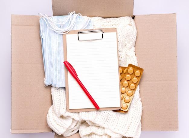 Sociale bijstand concept. in een kartonnen doos zit een leeg formulier, spullen, medicijnen en persoonlijke beschermingsmiddelen