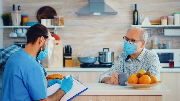 Sociale bijstand met gezichtsmasker en vizier die aantekeningen maken op het klembord terwijl ze tijdens huisbezoek met senior man nemen. verpleegkundige bij bezoek van gepensioneerd echtpaar met uitleg over verspreiding van covid-19, hulp bij risico's