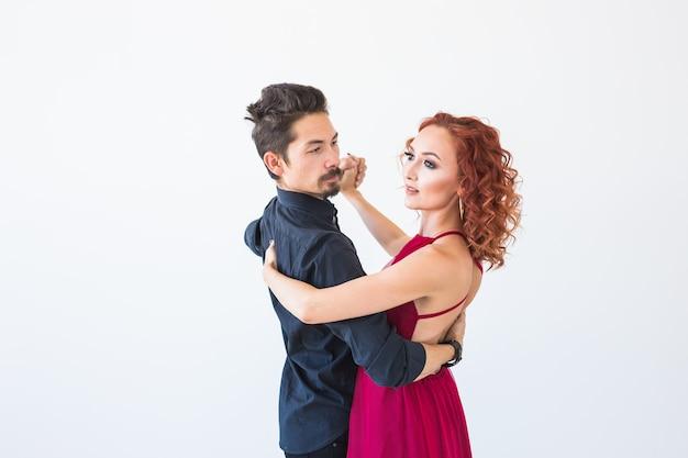 Sociale dans, bachata, kizomba, salsa, tangoconcept - vrouw gekleed in rode jurk en man in een zwart kostuum over wit oppervlak.