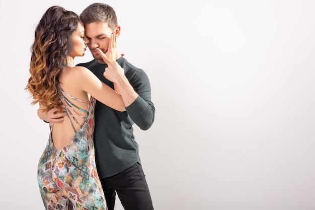 Sociale dans, bachata, kizomba, tango, salsa, mensenconcept - jong paar dat over witte muur met exemplaarruimte danst