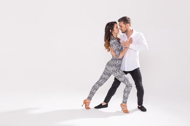 Sociale dans, bachata, kizomba, zouk, tango concept - man knuffelt vrouw tijdens het dansen op witte achtergrond met kopie ruimte