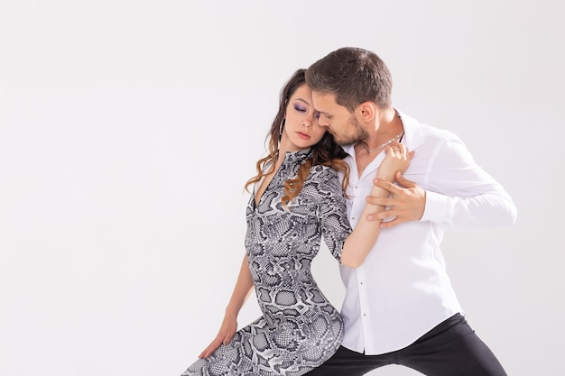 Sociale dans, bachata, kizomba, zouk, tango concept - man knuffelt vrouw tijdens het dansen over witte muur met kopie ruimte